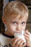 Boy with milk. Adorable boy with glass cup of milk Stock Photos