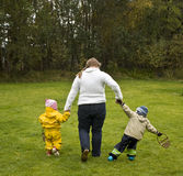 Boy misbehaving. Mother walking with two children. The girl walks nicely by her side, the boy is trying to run away Stock Photos