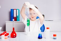 Boy mixing colored liquids in test tubes Stock Images
