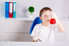 Boy mixing colored liquids in test tubes Royalty Free Stock Photography