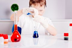 Boy mixing colored liquids in test tubes Stock Image