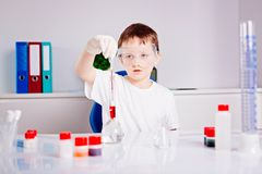 Boy mixing colored liquids in test tubes Royalty Free Stock Photos