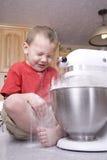 Boy mixing flour Stock Photography