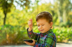 Boy with mobile phone. Cute little boy with mobile phone in summer park Royalty Free Stock Photo