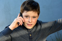 Boy with mobile phone. Friendly teenage boy telephoning with the mobile phone Royalty Free Stock Photos