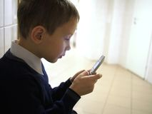 Boy with mobile phone sitting in policlinic. Child with old mobile phone sitting in policlinic Royalty Free Stock Images