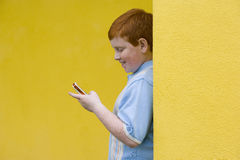 Boy (9-11) with mobile phone, smiling, side view Royalty Free Stock Photography