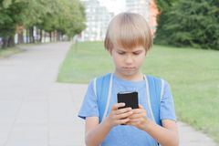 Boy with mobile phone in the street. Child looks at the screen, use apps, plays, writes or reads message. City background. School, Royalty Free Stock Images