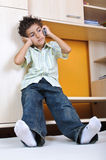 Boy with mobile phone talking indoor Royalty Free Stock Image