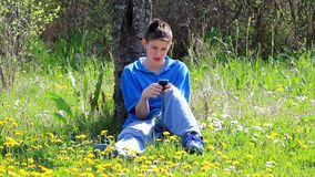 Boy with mobile phone.Teenage boy sitting outdoors using mobile phone stock video