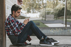 Boy with mobile phone. Teenager boy with mobile phone in the city Royalty Free Stock Images