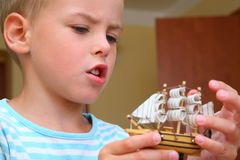 Boy with model of ship in hands Royalty Free Stock Photos