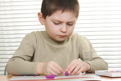Boy modelling at desk Stock Photo