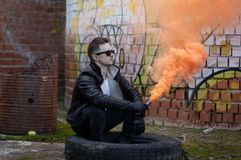 Boy with modern clothes and sunglasses with a smoke flare in an abandoned place stock images