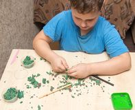 The boy is molding plasticine on the table.  Royalty Free Stock Image