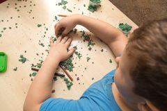 The boy is molding plasticine on the table.  Stock Photos