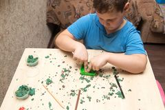 The boy is molding plasticine on the table.  Stock Photography