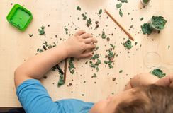 The boy is molding plasticine on the table.  Royalty Free Stock Images