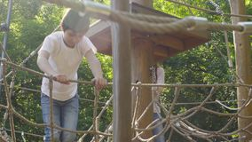 A boy and mom climbing on a playground equipment stock video
