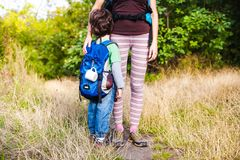 Boy and mom in the forest. A boy with a backpack is walking through the forest. The child is traveling with his mother. The kid is standing on a trail in the royalty free stock images