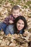 Boy and mom in leaves Royalty Free Stock Images