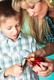 Boy with mom looking through a magnifying glass. Children development concept. Mother with son little boy examining apple looking through a magnifying glass Stock Image