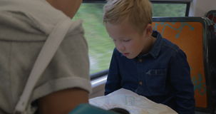 Boy with mom looking at map in train. Little boy and mother riding in the train and searching travel destination on the map stock video
