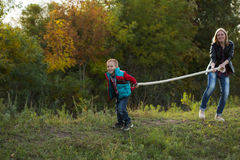 Boy and mom pulling the rope in nature in the autumn forest. Park, trying to win everyone smiling and laughing happily Royalty Free Stock Photography