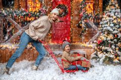 Boy with mom in yard. Mother and her son are playing in the yard of their house decorated for Christmas. Family miracle time. Merry Christmas and Happy New Year stock image