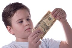 The boy and money. The little boy holds money and attentively them considers Royalty Free Stock Images