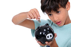Boy and money box Stock Photos