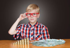 Boy with money. Portrait of a funny boy in red-framed glasses with cash banknotes and coins Stock Photography