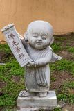 Boy monk statue at Hsi Lai Buddhist Temple, California. Hacienda Heights, CA, USA - March 23, 2018: Boy novice monk cement statue displaying tablet with Stock Photo