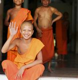Boy Monk Waving and Smiling in Cambodia Royalty Free Stock Photography