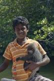Boy and Monkey. Hikkaduwa, Sri Lanka- March 03, 2012: Boy offering his monkey for photo Royalty Free Stock Photos