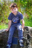 Boy on a monument. A cute smiling young little boy sitting on a large rock monument. Shallow depth of field Royalty Free Stock Photo