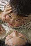 Boy and mother. Picture of a little chinese boy playing happily with his mother in bed Royalty Free Stock Image