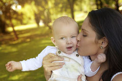 Boy and mother. Young woman kissing her baby son in the park Royalty Free Stock Photography