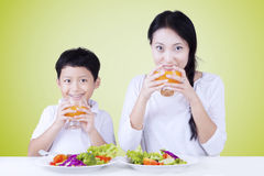 Boy with mother eat salad and drink juice Royalty Free Stock Photo