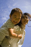 Boy and mother having fun on lawn. Picture of a little chinese boy having great fun on mother's back in a sunny autumn day on lawn Royalty Free Stock Image