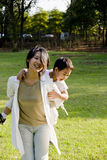 Boy and mother having fun on lawn. Picture of a little chinese boy having great fun on mother's back in a sunny autumn day on lawn Royalty Free Stock Images