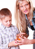 Boy with mother hold sling shot and mandarine. Stock Photos
