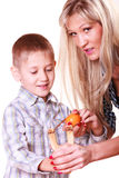 Boy with mother hold sling shot and mandarine. Royalty Free Stock Photo
