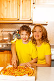 Boy and mother looking forward slicing pizza Stock Photography