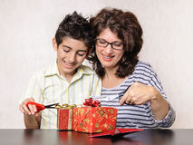 Boy and mother opening Christmas present Royalty Free Stock Images