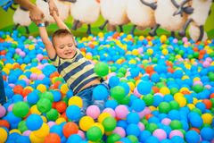 A boy with mother in the playing room with many little colored balls Royalty Free Stock Image