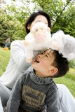 Boy and mother playing together. A picture of a little chinese boy and his mother playing plush toys together and having great fun Royalty Free Stock Image
