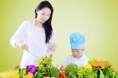 Boy and mother preparing salad Stock Photos