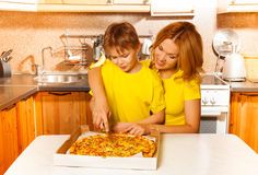 Boy and mother slicing pizza together in kitchen Stock Image
