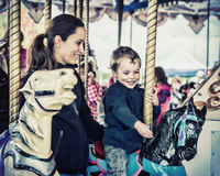 Boy and Mother Together on a Carousel Ride - Retro Royalty Free Stock Photos
